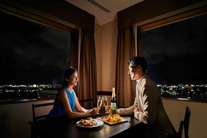 オークスカナルパークホテル富山のスイートルームでディナーを楽しむ男女2人