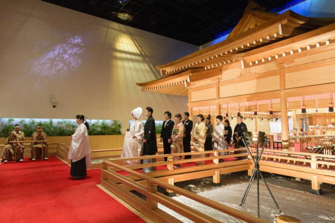 神殿の中を並んで歩く新郎新婦と参列者たち
