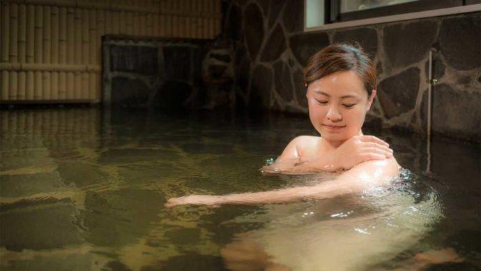 人吉温泉 相良路の湯 おおがの温泉に浸かる女性