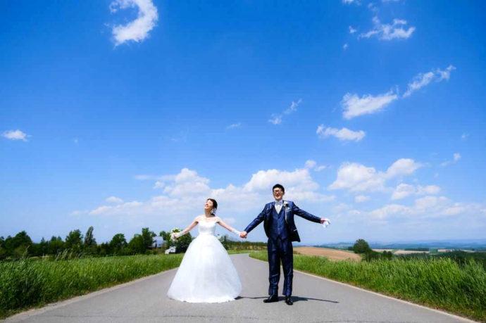 北海道「美瑛の丘」で両手を広げる男女2人