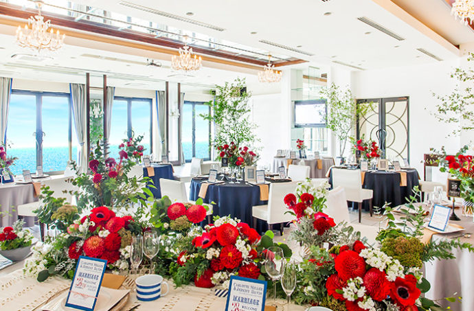 赤い花が華やかに飾られたリヴァージュブランの披露宴会場