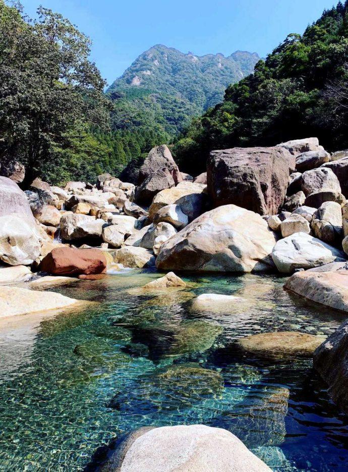 猿ケ城渓谷の透明な水と遠くに見える「刀剣山」