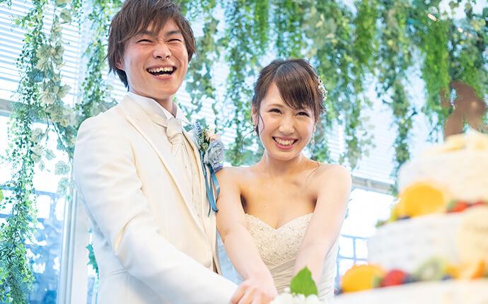 夫婦が結婚式でケーキを入刀しているときのイメージ