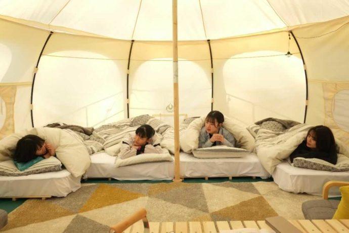 ひるぜん塩釜キャンピングヴィレッジにあるロータスベルテントでベッドに横たわる女性たち