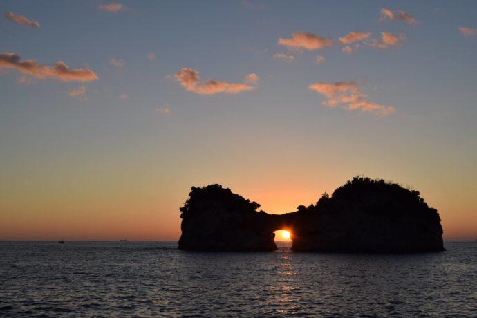 和歌山県の人気観光スポット・円月島の海蝕洞に沈む丸い夕日