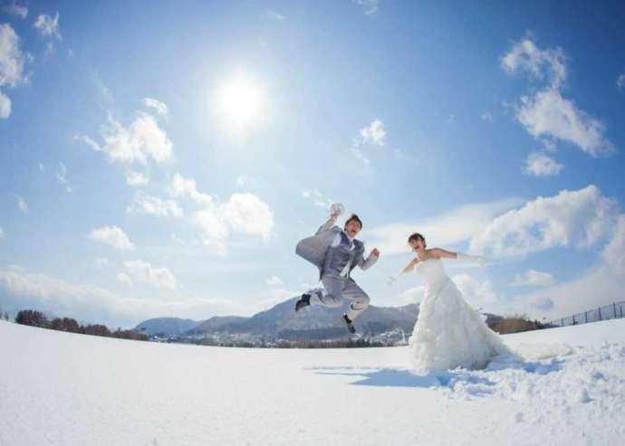函館山と雪を背景に撮影した洋装でのウェディングフォト