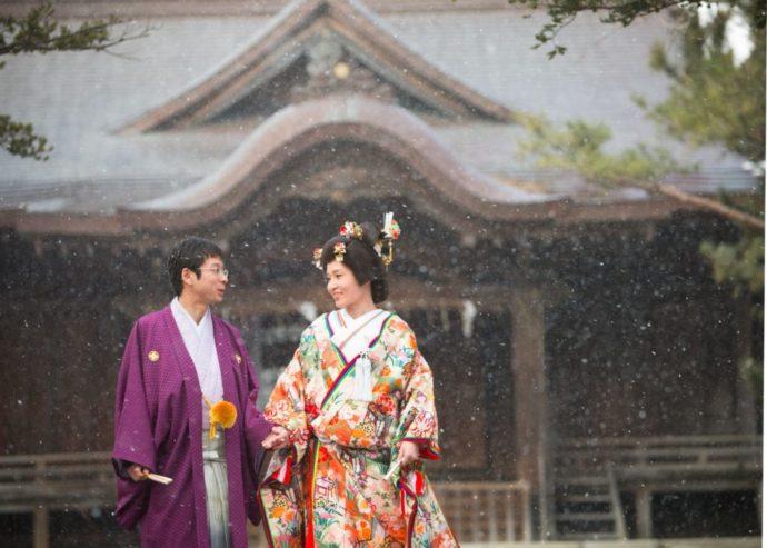 降雪の中で撮る神社境内での結婚写真