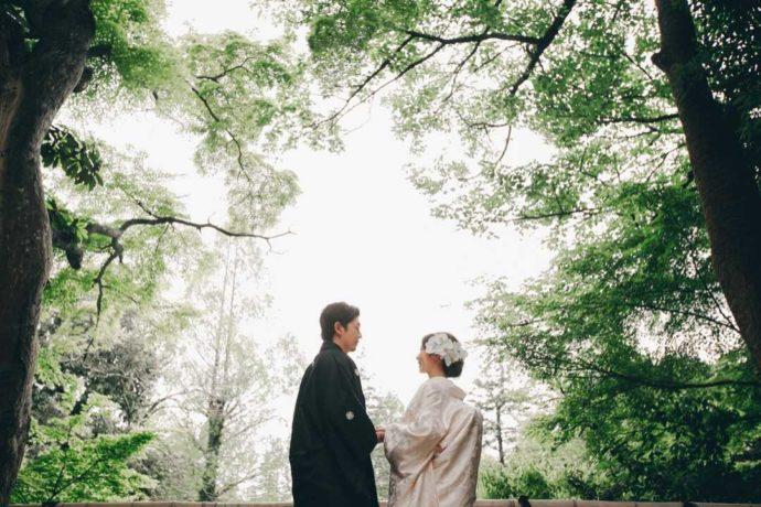 緑の木々に囲まれて手を取り合う和装姿の新郎新婦