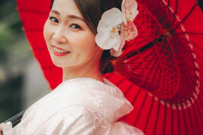 赤い番傘をさして微笑む和装姿の新婦