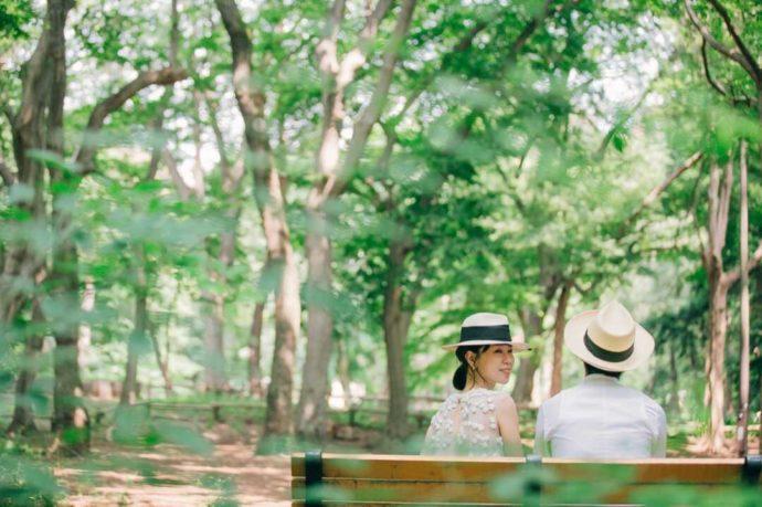 緑あふれる木々とベンチに座る新郎新婦