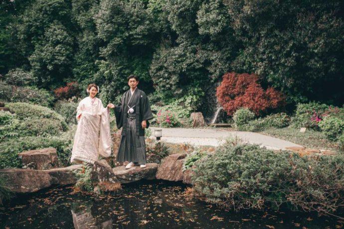 池の縁で手を取り合う和装姿の新郎新婦