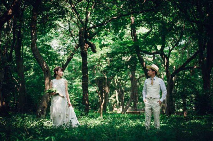 緑の森の中で佇むウエディングドレスとタキシードの新郎新婦
