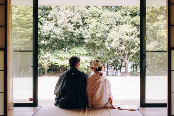 縁側に座り庭を眺める白無垢花嫁と羽織花婿の後ろ姿