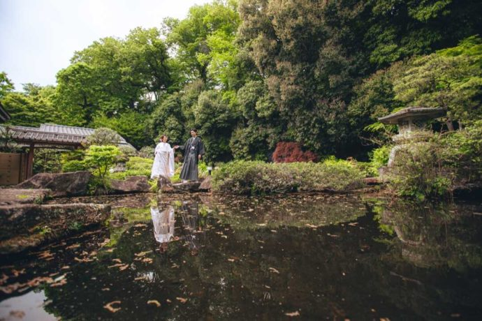庭園の池の縁を手を取り合って歩く和装姿の新郎新婦