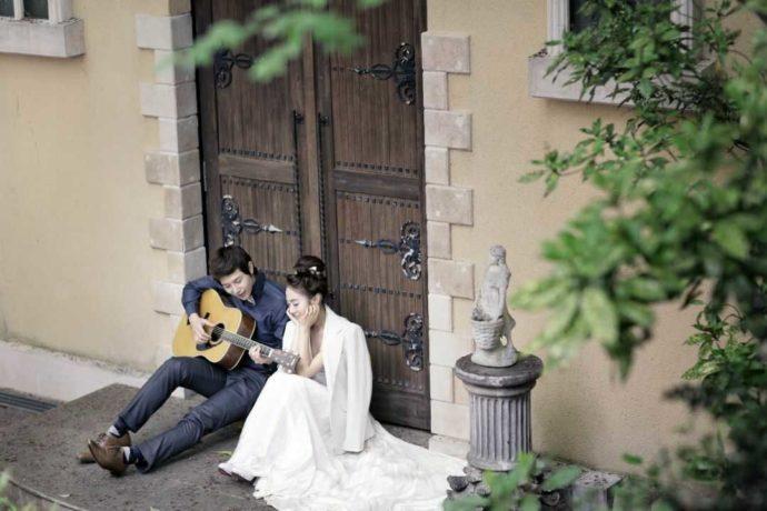 LUXEのフォトウェディングでギターを弾く新郎とうっとりする新婦