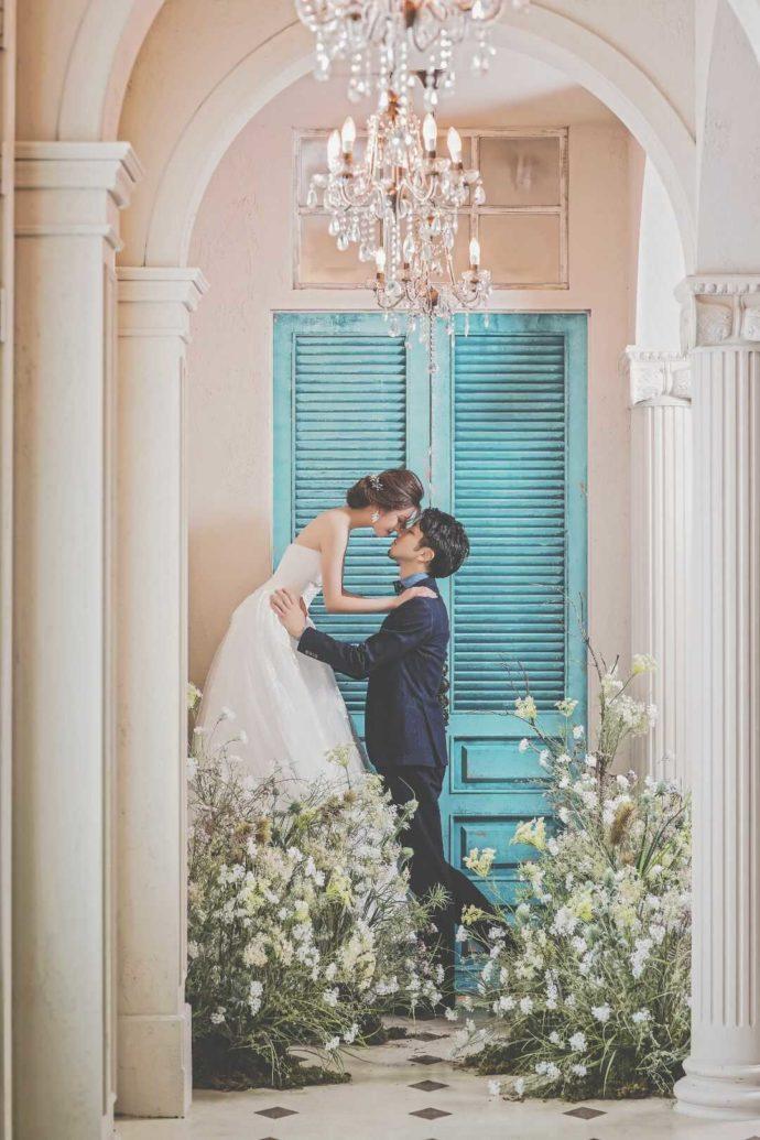 LUXEのセットで可愛らしい水色の扉をバックに写真を撮る新郎新婦