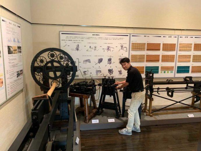 すだれ資料館で竹ひごを作る機械を紹介する増井さん