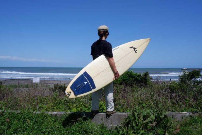 「シーサイド太東海岸バーベキュービレッジ」から歩いて行ける海を眺めながらサーフボードを持って立つ1人の男性