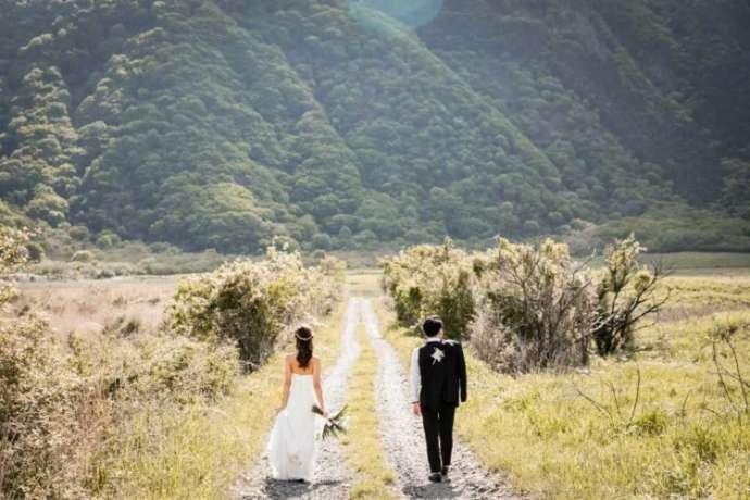 大自然の中で2人で同じ方向を向きたたずむ新郎新婦