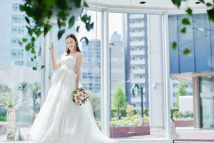 純白のドレスを着てブーケを持つ新婦