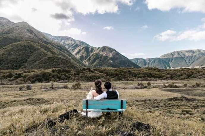 大自然の中、ベンチに座り寄り添う新郎新婦のバックショット