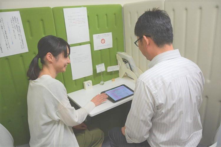 こうち出会いサポートセンターでタブレットの操作説明をする女性
