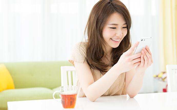 女性が笑顔でスマートフォンを触っているイメージ