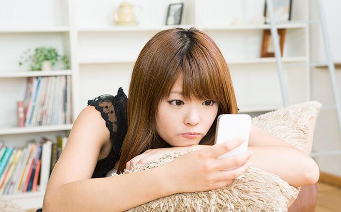 女性がスマートフォンを触っている時の画像
