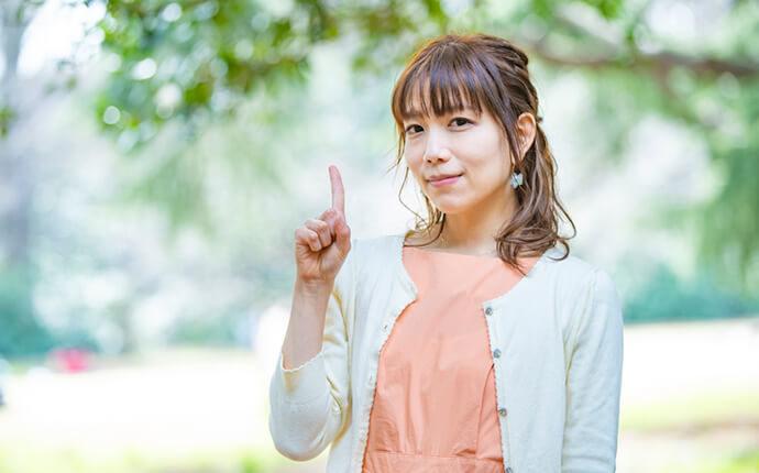 女性が人差し指を指しているイメージ
