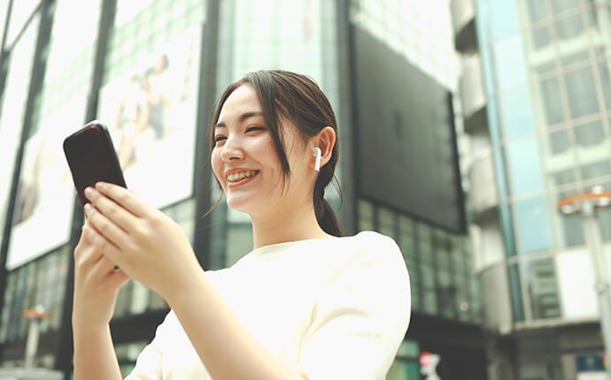 街中で女性がスマートフォンを触っているときのイメージ